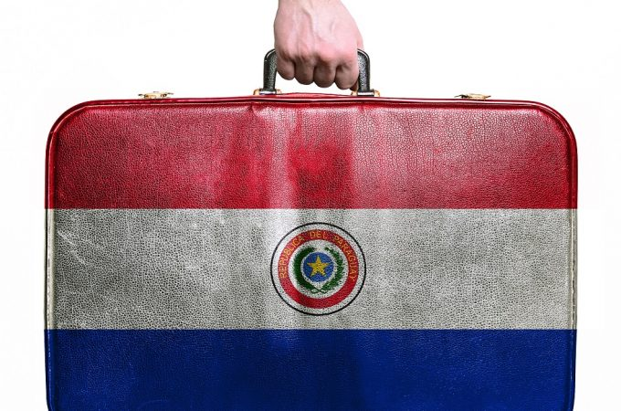 Tourist hand holding vintage leather travel bag with flag of Paraguay
